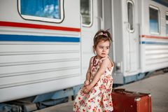 Little beautiful girl in retro dress says goodbye at the station with a little boy in vintage clothes with retro suitcase.  stock image