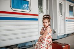 Little beautiful girl in retro dress says goodbye at the station with a little boy in vintage clothes with retro suitcase.  royalty free stock image