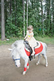 Little beautiful girl rides white pony. In woods at summer day Stock Image