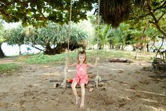 Little beautiful girl riding on swing on sand background, wearing pink dress. royalty free stock photos