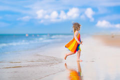 Little beautiful girl running on a beach Stock Photo