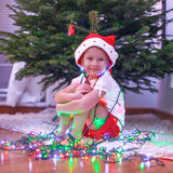 Little beautiful girl in Santa Claus hat sitting Royalty Free Stock Image