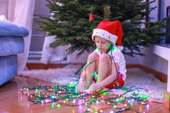 Little beautiful girl in Santa Claus hat sitting Royalty Free Stock Images