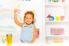 Little beautiful girl shows card with letter Royalty Free Stock Image