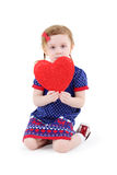 Little beautiful girl sits with red heart and looks at camera stock photo