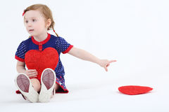 Little beautiful girl sits with red heart Royalty Free Stock Photos