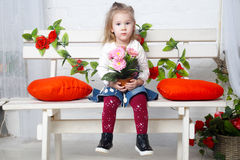 Little beautiful girl is sitting on the bench Royalty Free Stock Photo