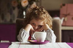 Little  beautiful girl sitting at the kitchen table Royalty Free Stock Image