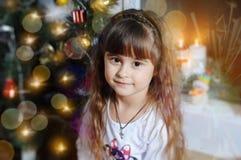 Красивая девочка сидит возле новогодней елочки royalty free stock photos