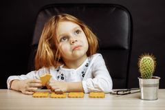 Little beautiful girl sitting at the white table close up portrait stock photography