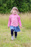 Little beautiful girl in skirt going and hamming at green meadow Royalty Free Stock Photography