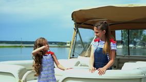 The little beautiful girl in the slowed-down movement is turned around herself near boats at water. Two sisters are. On this video you can see as the little girl stock video