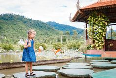 Little beautiful girl standing with a bottle of fish food in hand. Yang Bay Vietnam royalty free stock photo