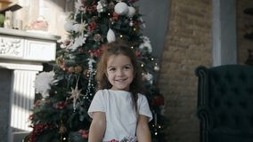 Little beautiful girl standing near a Christmas tree and holding a Christmas gift in the box stock video
