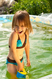 Little beautiful girl in swimming pool. Summer and sunshine. Little beautiful laughing loudly girl in outdoor small swimming pool royalty free stock images