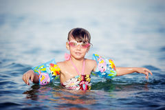 Little beautiful girl swims and dives to the sea Stock Image