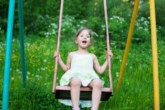 Little beautiful girl swinging in park Stock Image