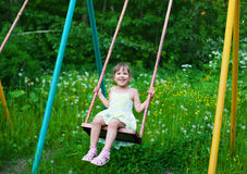 Little beautiful girl swinging in park Royalty Free Stock Image