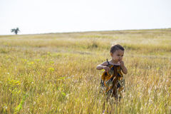Little beautiful girl walks through tall, autumn grass Royalty Free Stock Photos