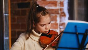 A little beautiful girl in white sweater playing violin stock footage