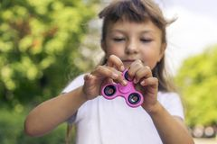 Little beautiful girl in white t-shirt is playing pink spinner in hand on the street stock images