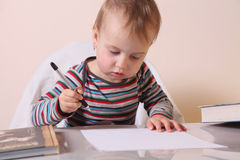 Little beautiful girl writing in her book Stock Images