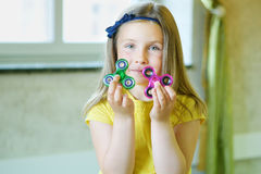 Little beautiful girl in yellow t-shirt is playing with two spinners in hands Stock Image