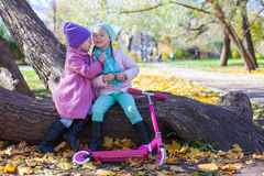 Little beautiful girls with scooter in the autumn Royalty Free Stock Image