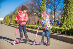 Little beautiful girls with scooter in spring park. Little beautiful girls with scooter in the park Stock Photography