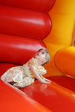 Little beautiful happy girl lies in bouncy castle Stock Photography