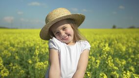 Little beautiful happy girl smiles in a yellow field hides behind a bouquet of yellow flowers