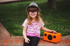 Little hipster girl listens music on wireless retro looking spea Royalty Free Stock Images