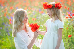 Little beautiful kid girl giving a flowers to her smiling mother. Happy people outdoors Stock Photography