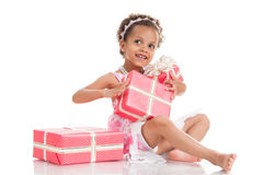 Little beautiful mulatto girl with gifts. Royalty Free Stock Images