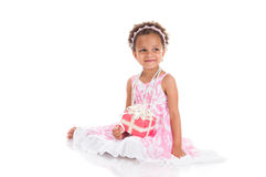 Little beautiful mulatto girl with gifts. Royalty Free Stock Photography