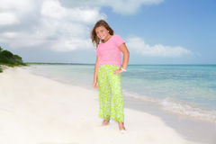 Little beautiful pretty fashionable girl standing on Cuban beach against turquoise ocean and blue sky background Stock Photography