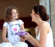 Little beautiful pretty girl giving a gift to her happy mother. Daughter gives mom a gift and they laugh Royalty Free Stock Photography