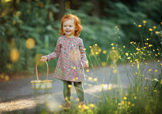 Little beautiful red-haired girl baby girl smiling, in summer in Stock Photo
