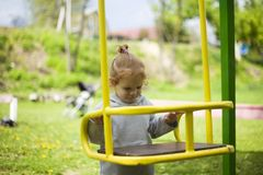 Little beautiful red-haired girl hung on a swing, baby plays on a swing on the playground stock images