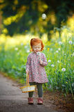 Little beautiful red-haired little girl blowing on dandelion, in Royalty Free Stock Image
