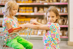 Little beautiful sisters in supermarket. Little beautiful sisters in modern supermarket with cart Stock Image