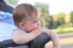 little, beautiful, smiling, cute redhead baby in a pram out-of-doors in a sleeveless shirt holding fingers in his mouth royalty free stock photo