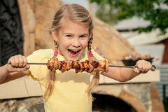 Little beautiful smiling girl with pleasure eats kebab outdoor a Stock Photo