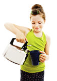 Little beautiful smiling girl pours tea from teapot into cup Stock Photos