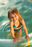 Little beautiful smiling girl in swimming pool. Summer and sunshine. Little beautiful laughing loudly girl in outdoor small swimming pool stock image
