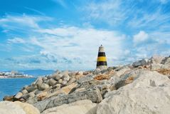 Little beautiful white, yellow and black lighthouse standing over the big stones at the pier of Benalmadena port, panoramic view stock photos
