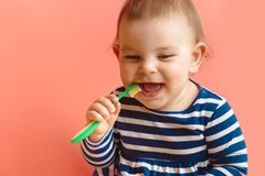 Little beautifulbaby toddler cleaning teeth with child brush on pink background happy face. Little beautifulbaby toddler cleaning teeth with child brush on pink royalty free stock image