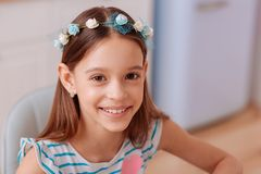 Close up of pleased kid that looking forward. Little beauty. Cheerful brunette girl expressing positivity while posing on camera royalty free stock image