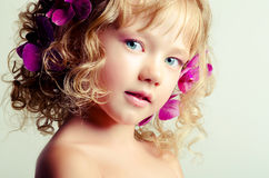 Little beauty girl with orchid flowers Stock Photo