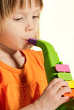 Little beauty girl with toy saxophone. In her hands on white background royalty free stock images